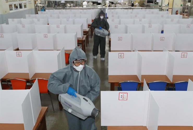 Quarantine officials disinfect a cafeteria in a high school in the southwestern city of Gwangju, Tuesday, a day before high schools reopen for seniors after multiple delays due to safety concerns over the spread of COVID-19. Yonhap