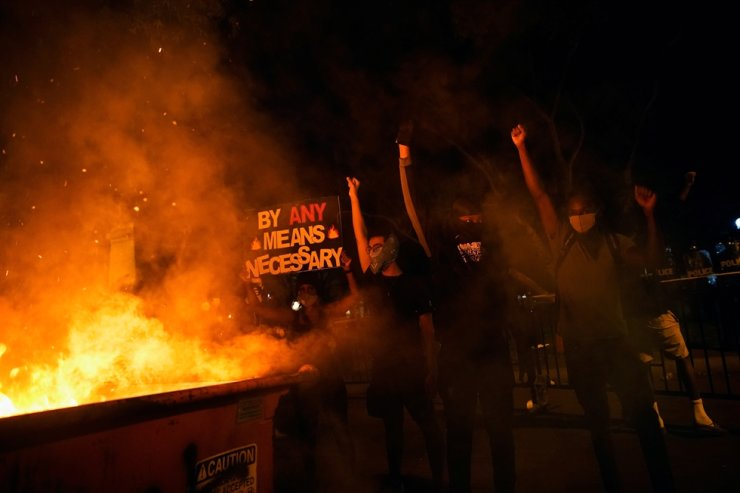 Demonstrators gesture and hold a sign next to a fire during a rally near the White House against the death in Minneapolis police custody of George Floyd in Washington, D.C. U.S. May 30, 2020. Reuters