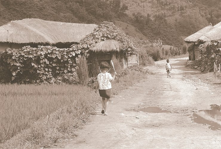 Two children walk on an unpaved road between thatch-roofed houses in Gangchon, Gangwon Province, near Bukhan River, in this 1968 photo taken by Japanese pastor Nomura Motoyuki. / Photo from Noonbit Publishing