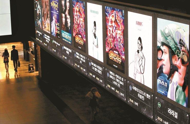Moviegoers walk through a relatively empty cinema foyer in Seoul, Friday. / Yonhap