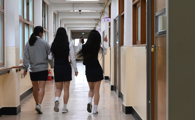 Students walk along the corridor of a high school in Seoul, Wednesday. South Korean schools reopened from Wednesday as the COVID-19 infection curve has flattened significantly and preventive measures for virus transmission are in full swing. Third-grade high school students are the first of those taking onsite classes, with lower graders set to follow in coming days under the phased reopening plan. Korea Times photo by Shim Hyun-chul
