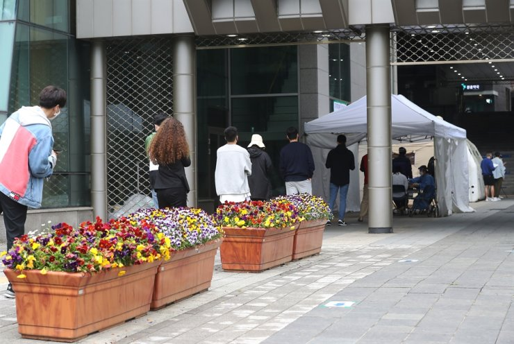People wait for COVID-19 testing at a screening center in a public health center in Yongsan, Sunday, amid growing fears of a cluster infection after a man in his 20s who went to clubs in Itaewon was confirmed to be infected last week. /Yonhap