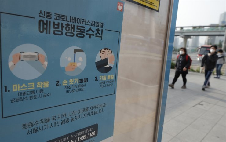 People wearing face masks walk near a banner showing precautions against the new coronavirus at a bus stop in Seoul, Monday, May 25, 2020. AP