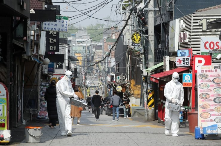 Officials from Yongsan District Office in Seoul disinfect an Itaewon street thick with bars and clubs, Monday. Yonhap