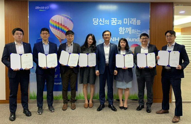 NH-Amundi Asset Management CEO Bae Young-hoon, fifth from left, poses with seven members of the investment firm's youth board, at the company's headquarters on Yeouido, Seoul, Thursday. / Courtesy of NH-Amundi Asset Management