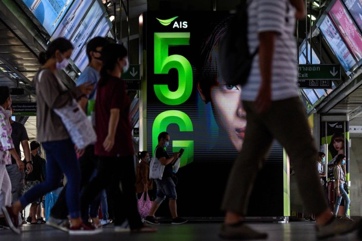 Commuters walk in front of a 5G advertisement screen at a train station in Bangkok last week. AFP-Yonhap