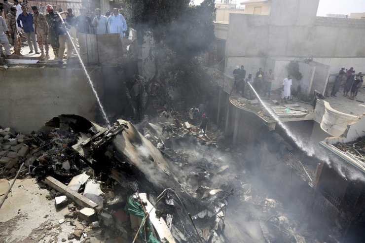Fire brigade staff try to put out fire caused by plane crash in Karachi, Pakistan, Friday, May 22, 2020. An aviation official says a passenger plane belonging to state-run Pakistan International Airlines carrying more than 100 passengers and crew has crashed near the southern port city of Karachi. AP