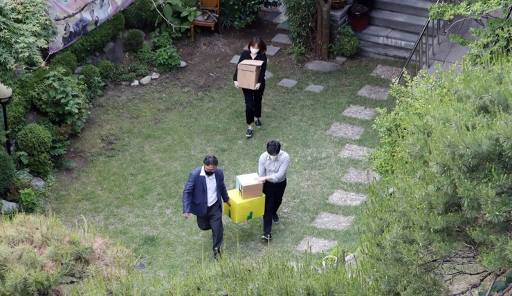 Prosecutors move boxes after completing their search-and-seizure operation, Thursday, at a shelter in Seoul operated by the Korean Council for Justice and Remembrance for the Issues of Military Sexual Slavery by Japan. The group is facing suspicions that it embezzled funds donated to help victims of Japan's wartime sex slavery. / Yonhap