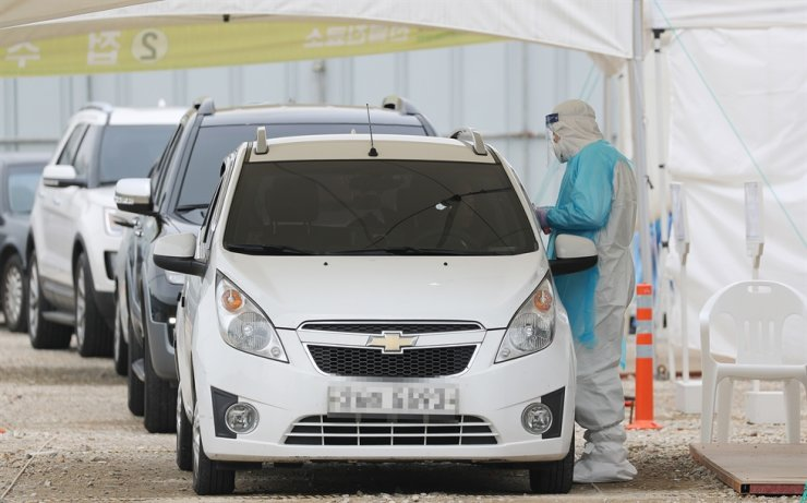 Cars line up at a drive-thru testing location for coronavirus at Ewha Womans University Seoul Hospital in Gangseo-gu, Seoul, Monday. Yonhap