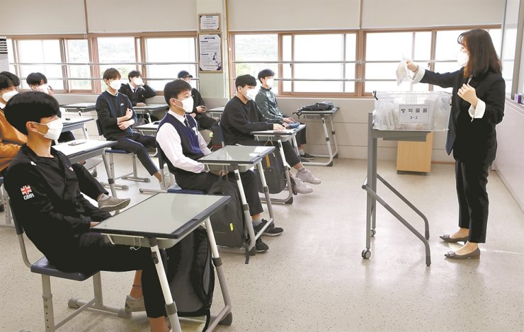 A teacher explains anti-COVID-19 procedures to students in a high school in Seoul, Wednesday, when schools across the nation reopened for high school seniors despite lingering COVID-19 fears. / Korea Times photo by Shim Hyun-chul