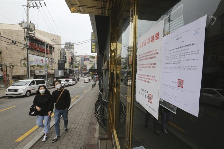 In this May 10, 2020, file photo, notices of the Seoul city emergency administrative order to prohibit gathering are posted at the entrance of a temporary closed dance club in Seoul. The sign reads: 'The Seoul city emergency administrative order to prohibit gathering.' AP