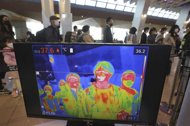 A thermal camera monitor shows the body temperature of passengers as they wait in line before boarding airplanes at the domestic flight terminal of Gimpo airport in Seoul, April 29. AP-Yonhap