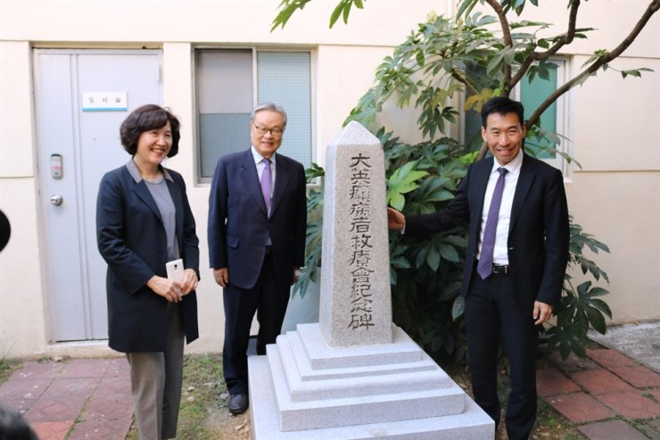 Australian Ambassador to Korea James Choi, right, stands with other dignitaries by a memorial honoring the now-demolished Busan Leper Hospital and its Australian founder, missionary James Noble Mackenzie, at a yard belonging to Ilsin Christian Hospital in Busan in 2017. / Courtesy of Embassy of Australia