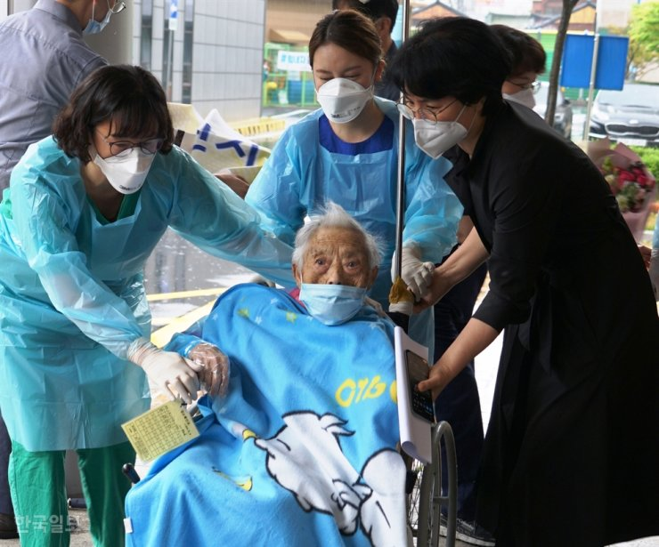 Choi Sang-boon is wheeled out of Pohang Medical Center on Friday, ending her two-month treatment in isolation for the coronavirus. Korea Times photo by Kim Jung-hye