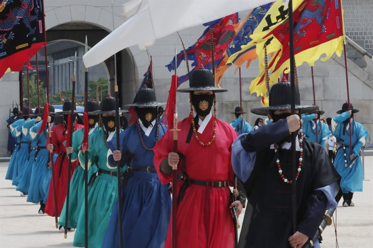 Korean Imperial guard waring face masks move during a reenactment of the Royal Guards Changing Ceremony, which had been suspended due to the new coronavirus, at Gyeongbok Palace in Seoul, Thursday, May 21, 2020. AP