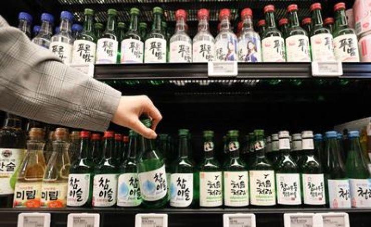 A customer picks up a bottle of soju at a shop in Seoul, April 28. / Korea Times file