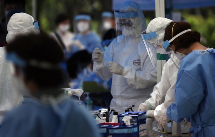 Health workers at a triage center for coronavirus testing in Jung-gu, central Seoul, Friday. Yonhap