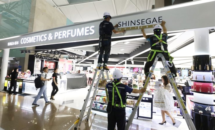 Workers put up signs at Shinsegae's duty free shop in Incheon International Airport prior to its opening in this 2018 file photo. / Yonhap