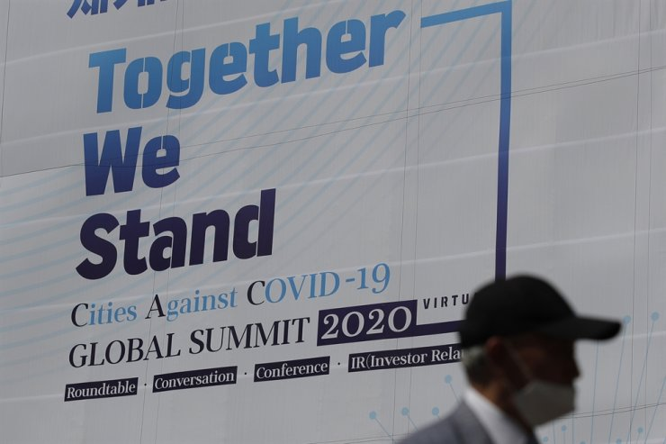 A man wearing a face mask as a precaution against the new coronavirus, walks by a banner about an international online conference in Seoul, Wednesday, May 27, 2020. AP
