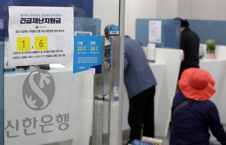 People seeking to take out loans stand in front of a teller at a branch of Shinhan Bank in Seoul, May 18. Korea Times file