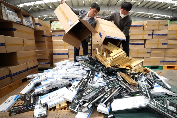 The boxes of Korean cigarette packs are piled up at the Busan Main Customs office in Busan, Wednesday. Port authorities said they have seized and destroyed about 640,000 trafficked cigarette packs worth 2.8 billion won. Yonhap