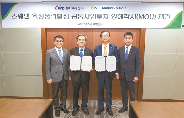 NH-Amundi Asset Management CEO Bae Young-hoon, second from right, and Korea Western Power Co. (KOWEPO) President Kim Byeong-sook, third from right, hold an MOU for a joint investment in a Swedish onshore wind-farm project at the headquarters of the asset manager in Seoul, last Friday. The wind-farm, set to be built by late this year in Ange municipality is expected to generate stable operating profits for dozens of years to come. / Courtesy of NH-Amundi Asset Management