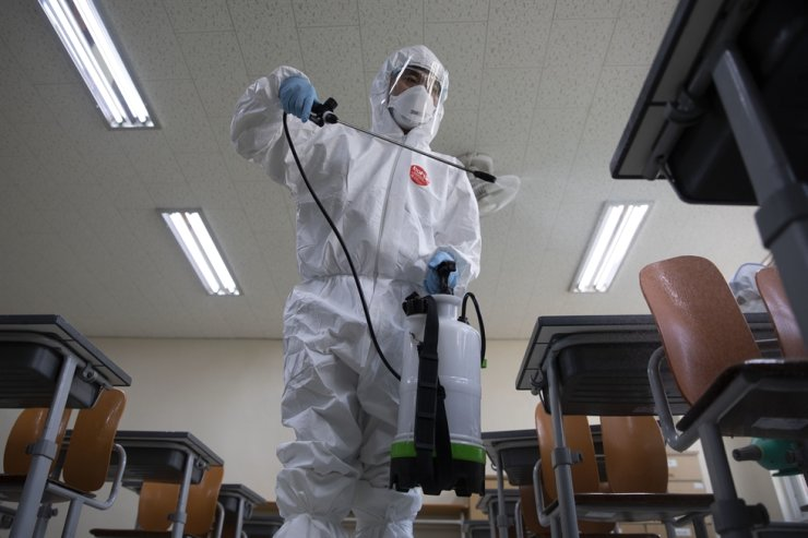A quarantine official disinfects a classroom at Yeongdongil High School in Songpa-gu, Seoul, Monday. The country will reopen schools in stages, starting with high school seniors, Wednesday. Korea Times photo by Choi Won-suk