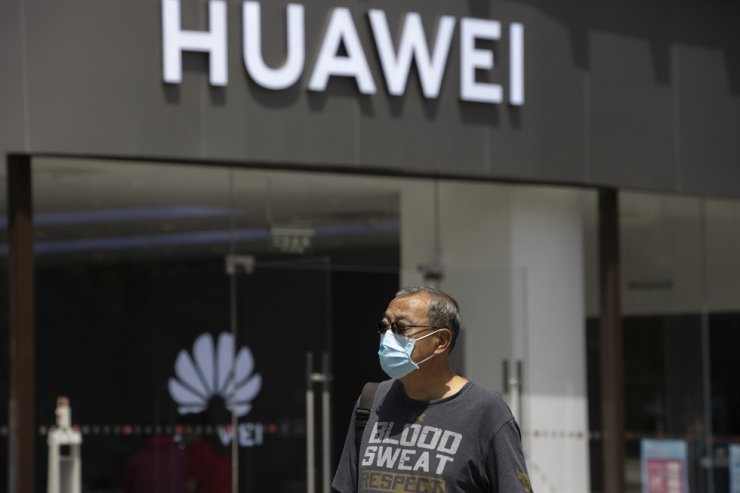 A man wearing a face mask to protect against the coronavirus walks past a Huawei retail store in Beijing on Monday, May 18, 2020. China's commerce ministry says it will take 'all necessary measures' in response to new U.S. restrictions on Chinese tech giant Huawei's ability to use American technology, calling the measures an abuse of state power and a violation of market principles. (AP Photo/Ng Han Guan)