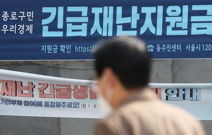 A citizen passes by a banner announcing the government's coronavirus relief funds in front of a community service center in central Seoul, Monday. / Yonhap