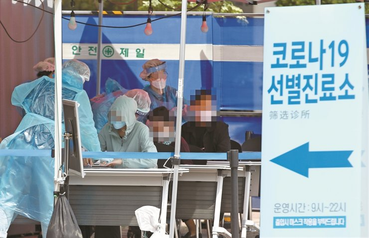 Medical staff at a public health center in Seoul's Yeongdeungpo District carry out coronavirus tests, Monday, after the country saw a sudden hike in the number of COVID-19 infections that were linked to nightclubs and bars in Itaewon. / Yonhap