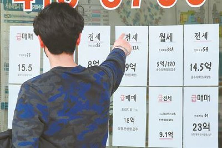 A man looks at apartment rent and sales offers put up in the front window of a realtors office in Seoul, April 21. Korea Times file