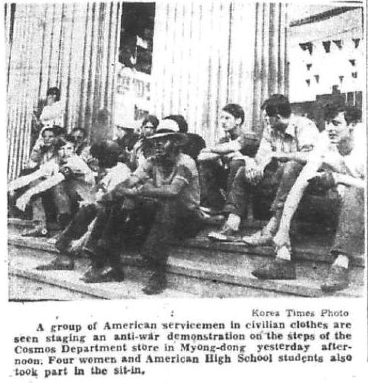 U.S. servicemen in civilian clothes stage an anti-war demonstration on the steps of Cosmos Department Store in Myeong-dong, May 18, 1971. / Korea Times archive