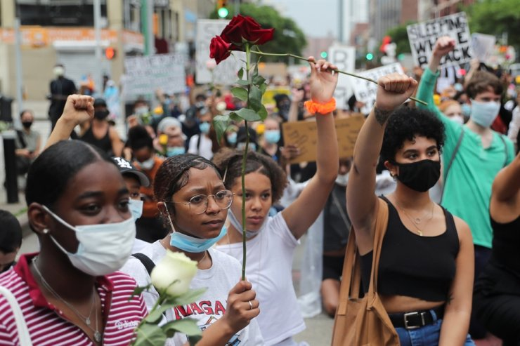Demonstrators kneel as they hold flowers during a protest against the death in Minneapolis police custody of George Floyd, in the Harlem neighborhood of Manhattan, New York City, June 5. U.S. health authorities worry that mass protests taking place across the country may lead to a new surge in COVID-19 infections in the coming weeks. Reuters