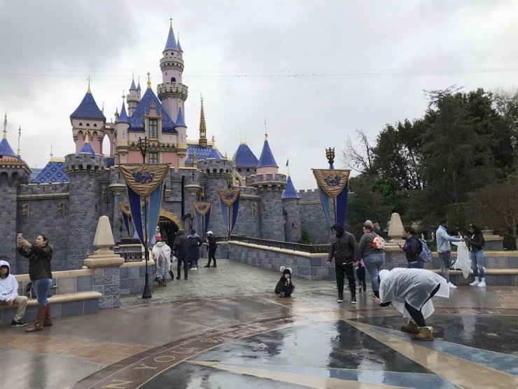 In this March 13, 2020, file photo, visitors take photos at Disneyland in Anaheim, Calif. Disney is proposing to reopen its Southern California theme parks in mid-July after a four-month closure due to the coronavirus, the company said on Wednesday, June 10, 2020. Disney is postponing the mid-July reopening of its Southern California theme parks until it receives guidelines from the state. The company announced Wednesday, June 23, 2020, an indefinite postponement for Disneyland and Disney California Adventure in Anaheim. (AP Photo/Amy Taxin, File)