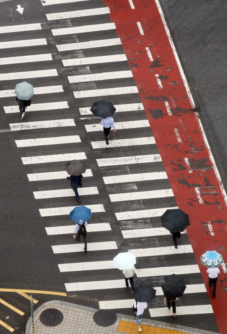 Citizens holding umbrellas cross the street at a crosswalk in central Seoul, Wednesday, as the early summer monsoon season began. The rain is expected to continue until early Friday, with another bout of monsoon rain expected from Sunday, according to the Korea Meteorological Administration. / Yonhap