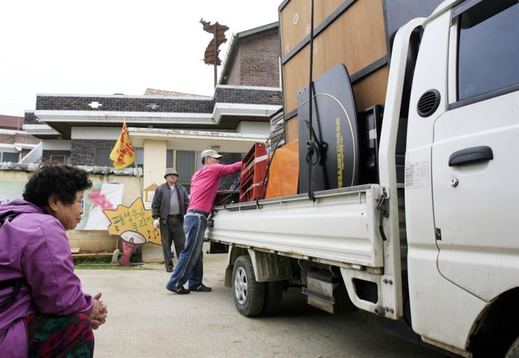 A resident of Daechu-ri village in Paengseong-eup, Pyeongtaek in Gyeonggi Province sees her furniture being loaded on a truck as she prepares to move from the town. Korea Times file