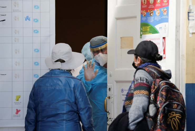 A health worker stops the entrance of patient relatives after the hospital was closed due to a reported outbreak of the coronavirus disease (COVID-19) amongst its medical staff, in La Paz, Bolivia June 16, 2020. REUTERS/David Mercado