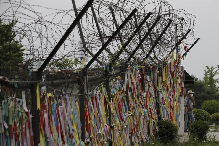 A man wearing a face mask walks near the wire fences decorated with ribbons written with messages wishing for the reunification of the two Koreas at the Imjingak Pavilion in Paju, South Korea, Thursday, June 18, 2020. AP