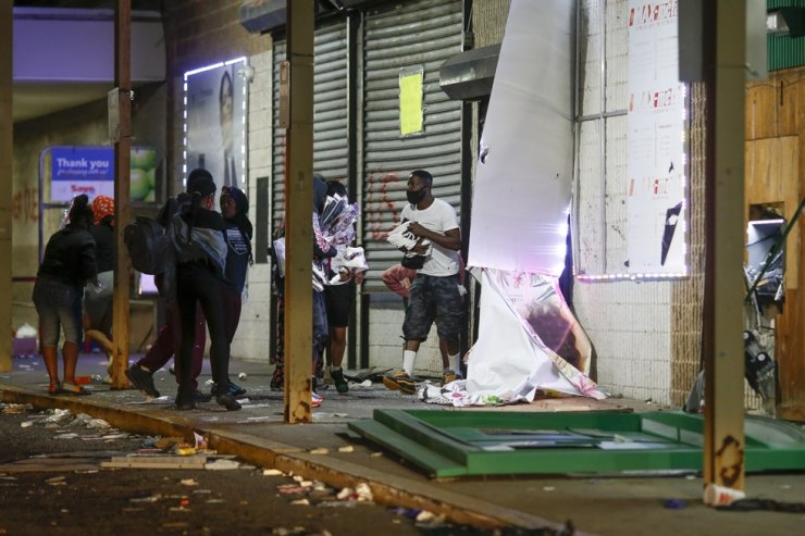 People carry packages near a security barrier on a window at a store in Philadelphia Sunday, May 31, as people protest over the death of George Floyd, a black man who was in police custody in Minneapolis. Floyd died after being restrained by Minneapolis police officers on Memorial Day, May 25. AP