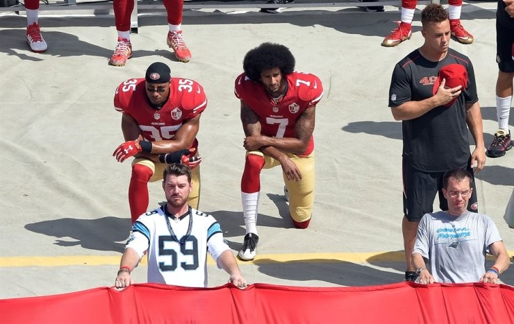 Colin Kaepernick (#7) and Eric Reid (#35) of the San Francisco 49ers kneel during the national anthem before their game against the Carolina Panthers at Bank of America Stadium in Charlotte, North Carolina, Sept. 17, 2016. / AFP-Yonhap
