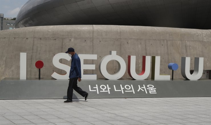 A man wearing a face mask walks in front of the display of South Korea's capital Seoul logo in Seoul, Sunday, June 28, 2020. AP