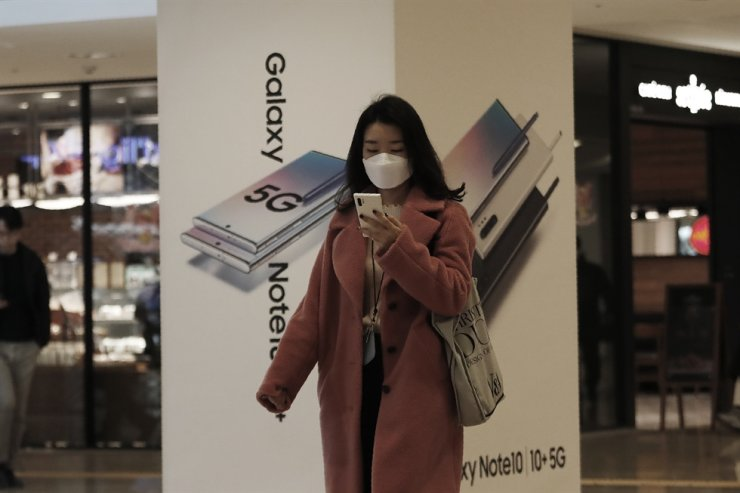 A woman passes by an advertisement of Samsung Electronics' Galaxy 5G Note10 smartphones at its shop in Seoul, Jan. 30, 2020. The company is expected to launch two new foldable smartphones this year. AP