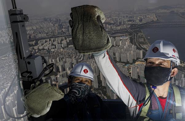Window cleaners are at work on the 123-story Lotte World Tower, Korea's tallest building, in southern Seoul, Tuesday. The skyscraper has about 42,000 windows. After opening to the public in 2017, the building has its windows cleaned once a year. Korea Times photo by Shim Hyun-chul