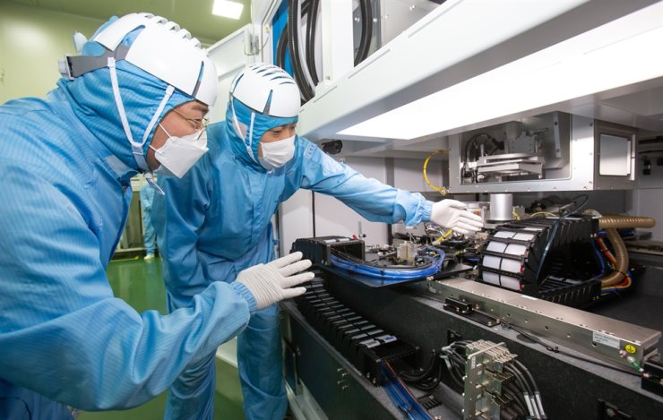 Semiconductor engineers from Samsung Electronics, left, and its partner company EO Technics, inspect laser equipment used for manufacturing chips, Thursday. / Courtesy of Samsung Electronics