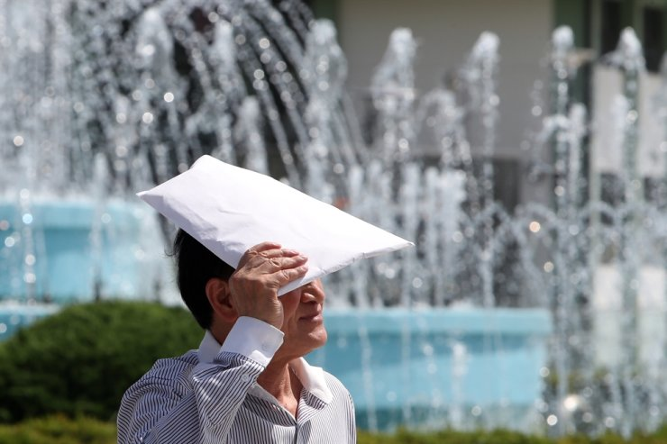 A man covers his head with a paper envelop to cool himself at a public park in Gwangju, Thursday. Yonhap