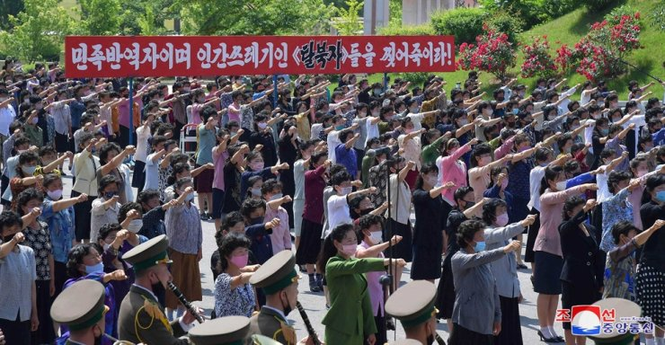 Officials and members of North Korean women's unions stage a mass rally outside a museum in Sinchon, South Hwanghae Province, Tuesday, to denounce the South Korean government and North Korean defectors here for their anti-Pyongyang leaflet campaigns. / Yonhap