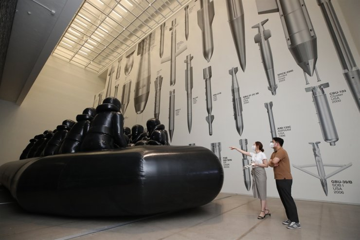 Visitors take a look at Chinese artist and activist Ai Weiwei's 'Law of the Journey' and 'Bombs' on view at the 'Unflattening' exhibition at the National Museum of Modern and Contemporary Art, Seoul, Tuesday. Yonhap