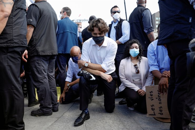 Canada's Prime Minister Justin Trudeau wearing a mask takes a knee during a protest against police brutality and racism following the death of George Floyd on Parliament Hill, in Ottawa, Ontario, Canada, June 5, 2020. Reuters