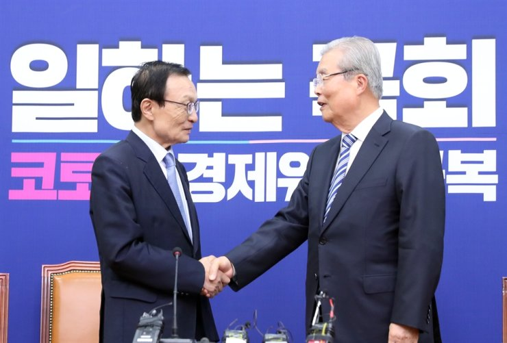 Lee Hae-chan, left, chairman of the ruling Democratic Party of Korea, shakes hands with Kim Chong-in, head of the main opposition United Future Party's emergency committee, during the latter's courtesy visit at the National Assembly in Seoul, Wednesday. They discussed pending issues regarding the opening session of the Assembly and the government's plan to allocate a third supplementary budget in response to the economic fallout of the COVID-19 pandemic. / Yonhap