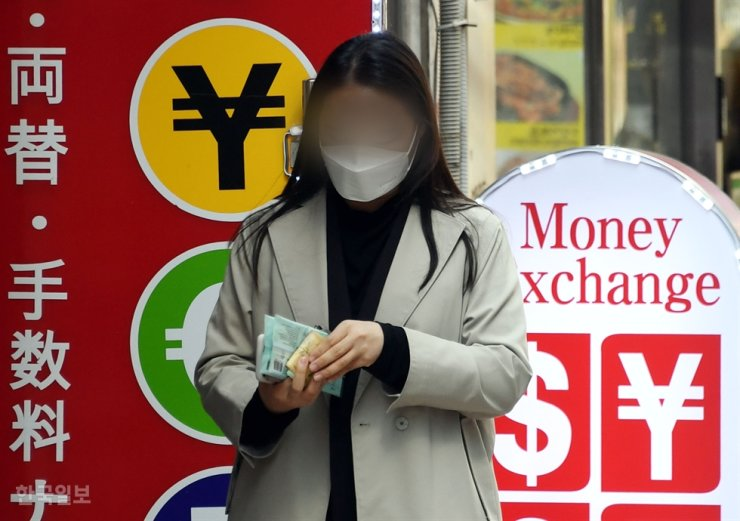 A woman checks her money in front of a currency exchange in Myeong-dong, downtown Seoul, in this March 23 file photo. / Korea Times photo by Ko Young-kwon